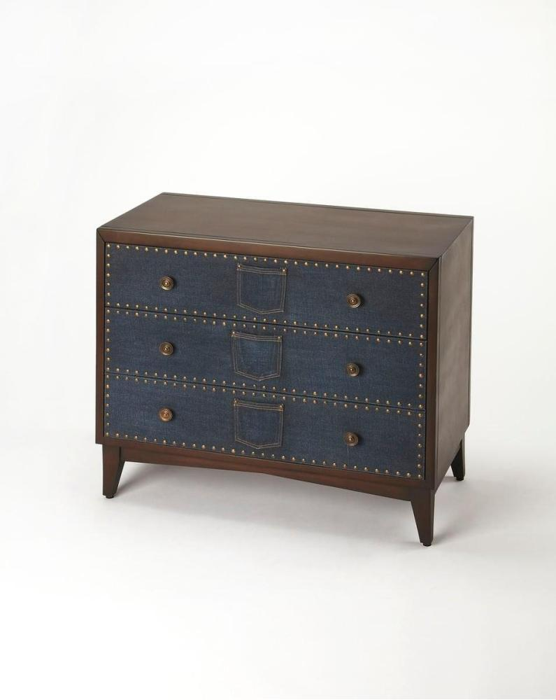 Whimsical and modern, this unique console chest is sure to be the focal point of any space. Expertly crafted from gemelina wood solids and wood products, its indigo blue denim drawer fronts are embellished with antique brass finished nailhead trim and mat