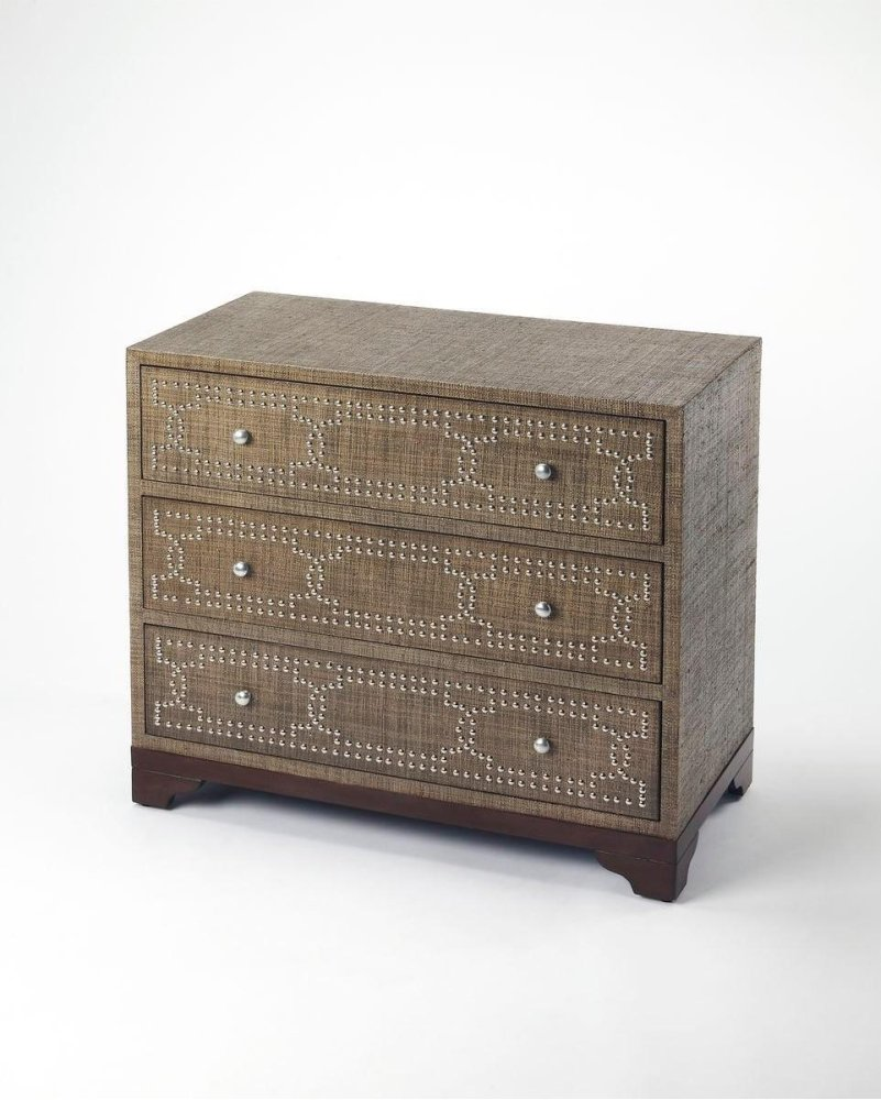 Woven raffia infuses organic texture to this sleek modern three drawer console chest. Expertly crafted from mahogany wood solids and wood products, the top, side and front surfaces are wrapped in raffia dyed to a hue of dark coriander. Including three spa