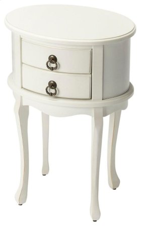 This charming oval side table combines elegant design details with convenient storage. It features a vibrant Cottage White finish with light distressing. Hand crafted from select hardwood solids and wood products, it includes two drawers with antique bras