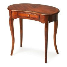 This elegant Writing Desk features a crescent shape tabletop supported by four stylized, tapered cabriole legs and a drawer with antique brass-finished hardware. It is crafted from solid poplar and cherry veneer in our Antique Cherry finish.