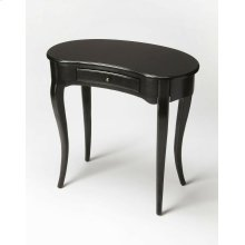 This elegant Writing Desk features a crescent shape tabletop supported by four stylized, tapered cabriole legs and a drawer with antique brass-finished hardware. It is crafted from solid poplar and cherry veneer in a Black Licorice finish.