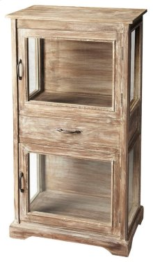 The light Artifacts finish of the Hardin display cabinet gives it a rustic look. The two large display shelves are separated by a large drawer for storage.
