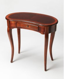 This elegant Writing Desk features a crescent shape tabletop supported by four stylized, tapered cabriole legs and a drawer with antique brass-finished hardware. It is crafted from solid poplar and cherry veneer in a rich Plantation Cherry finish.
