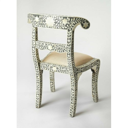 Hand-carved in captivating botanical shapes, each bone tile adorning this accent chair is individually cut, applied and offset by a gray resin background. Topped with a ivory fabric, padded seat cushion, this artisanal piece proves to be as comfortable as