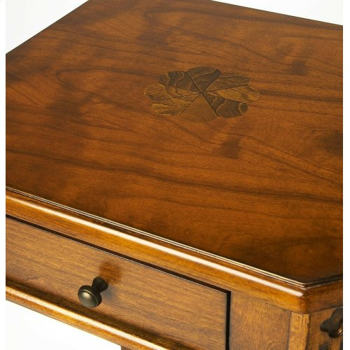 Selected solid woods and choice veneers. Hand carved details. Cherry veneer top with maple veneer inlay design. One drawer with antique brass finished hardware.