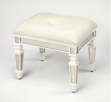 This glamorous vanity stool offers vintage style with antique mirror inlays along its apron and legs and an ivory button-tufted cotton upholstered seat. A captivating addition to any bedroom, bathroom, hall or entryway, it is hand crafted from poplar hard