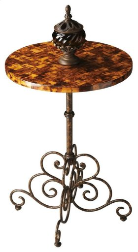 A simple pedestal connects the enticing tabletop handcrafted from coco bark and laminated for sheen and durability with a fanciful, swirling metal base atop bun feet.