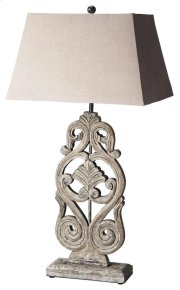 This distinctive table lamp will brilliantly light any space. Featuring a cathedral gray finish, it is hand crafted from mango wood solids with an iron harp and cotton shade. Product Image