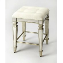 This glamorous counter stool delivers vintage style to your home with antique mirror inlays along its legs and apron and a tufted cotton upholstered ivory cushion. It is hand crafted from select hardwood solids and wood products featuring a pewter finish