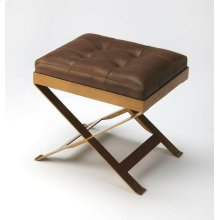 An updated version of the humble campaign stool, this charming ottoman adds extra seating and extra charm with buttery soft leather, hand-tufted in rich caramel. Brass finished metal frame adds durability, perfect for layering with a cozy throw or add a