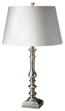 This modern table lamp will brilliantly light any space. Featuring a tarnished silver finish, it is hand crafted from aluminum with an iron harp and cotton shade.