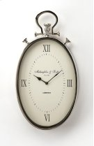 This wall clock is crafted in a vertical oval shape that features Roman numerals over a white face, and a sturdy handle. The clock can be placed on any wall and blends with a variety of decor. Makes a great gift. Product Image