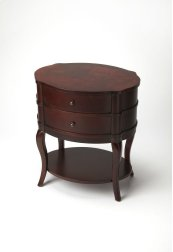 With polished curves and subtle finesse, this transitionally styled table has a sleek,functional design that suits almost every décor. Featuring a Plantation Cherry finish and two drawers with antique brass-finished hardware plus a bottom shelf, this clas