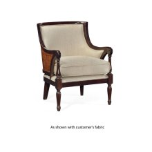 Armchair with rounded back and carved front legs, upholstered in COM