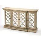 With four mirrored glass-paneled doors overlaid with intricate curved fretwork, this glamorus sideboard brings class and storage to any dining, living room or entry. Featuring four doors an interior shelf, tailored molding, and a distressed neutral finish Product Image