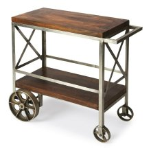 """Serve guests in style with this modern industrial trolley cart. Forged from iron, its frame has a zinc silver finish with stylish """"X """" side panels, and the mango wood top and bottom shelf have a vintage butcher block look in a clove brown finish. Use i"""